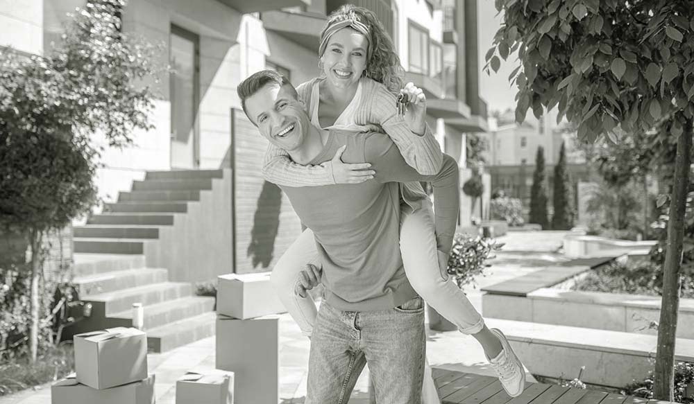 Woman and man smiling, surrounded by moving boxes, holding the keys to their new condo after a home inspection